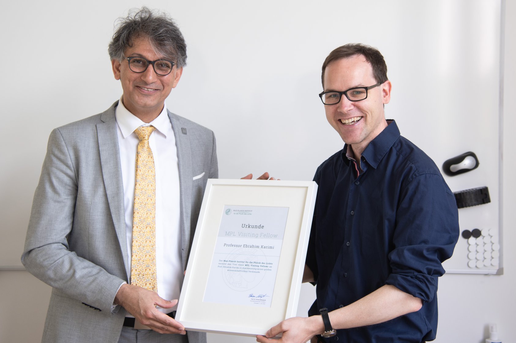 Prof. Ebrahim Karimi (left) and Prof. Florian Marquardt (right) holding a copy of Prof. Karimi's award