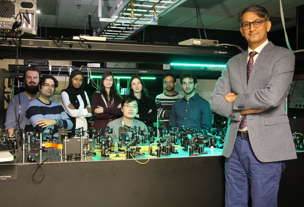 Ebrahim Karimi in his lab surrounded by his research group
