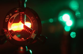 An orange light inside a metal disc projecting a green light