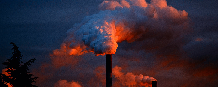Blue and red smoke pours out of a smoke stack
