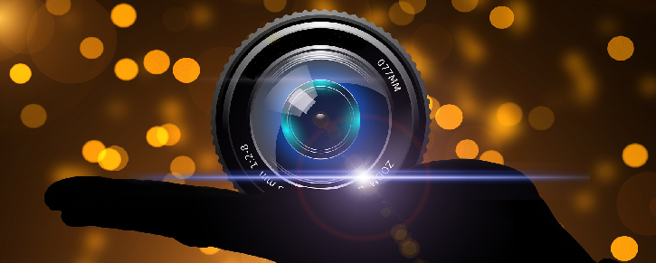 Black coloured hand holding a black camera lens surrounded by orange light pixels