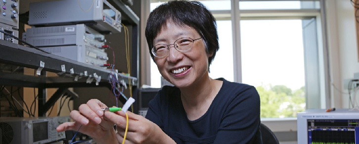 Xiaoyi Bao seated in her lab holding a fibre optic cable